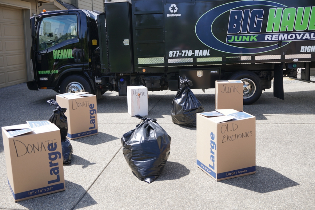 Garbage and donations being put into a junk removal truck