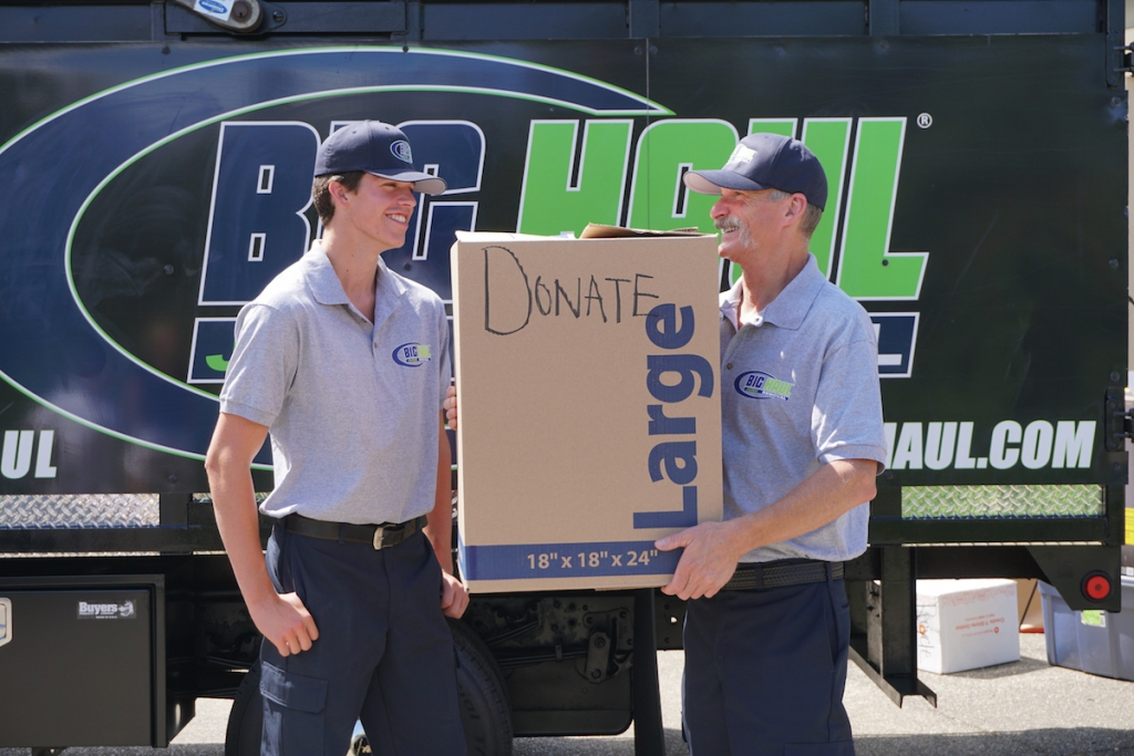 Two employees performing junk removal services